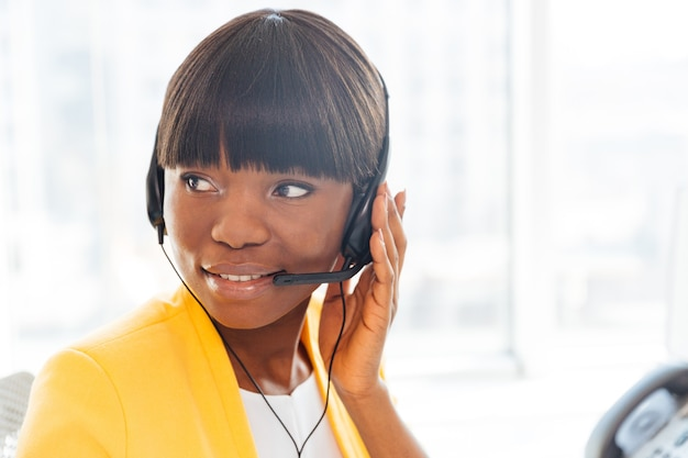 Happy businesswoman working in call center and looking away