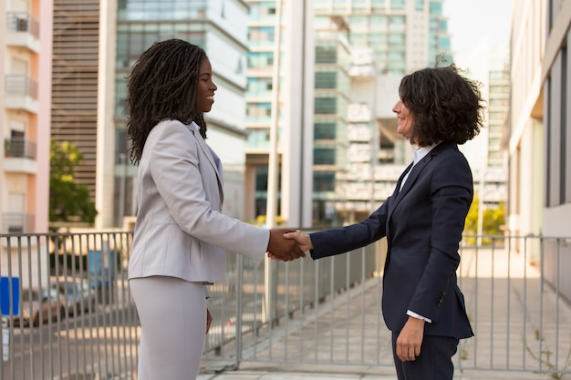 Happy businesswomen shaking hands outside