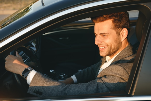 Happy bussinesman in suit driving