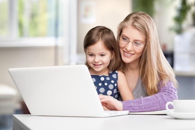 노트북에서 아이와 함께 일하는 행복한 바쁜 어머니