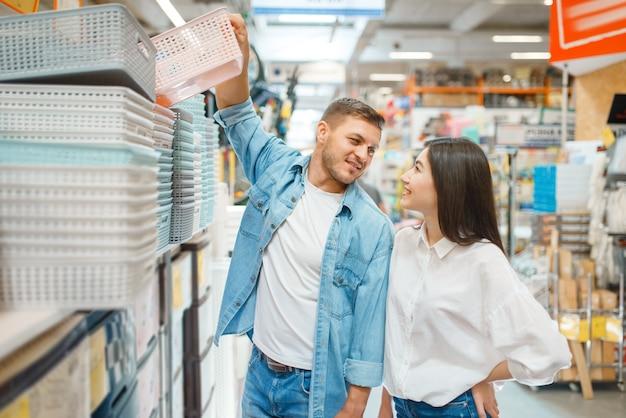 Счастливый покупатель берет корзину для стройматериалов в строительном магазине.
