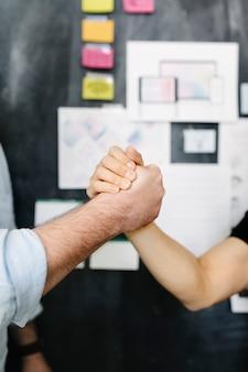 Счастливые коллеги, взявшись за руки в офисе