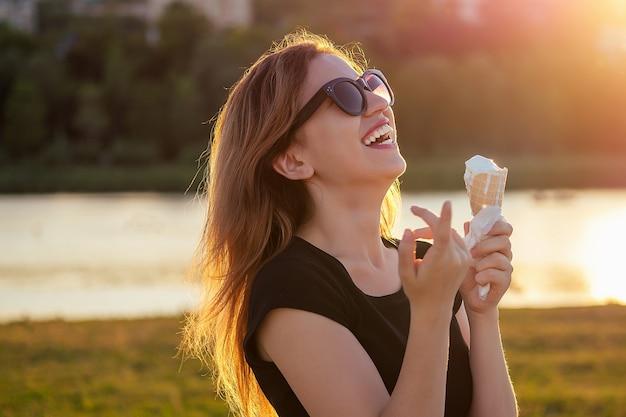 日光浴で幸せなカリフォルニアの美しい女性は、ビーチで日没時にワッフルホーンコーンでアイスクリームを食べます。夏の公園での女の子のクールな写真撮影。