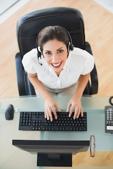 Happy call center agent typing while on a call
