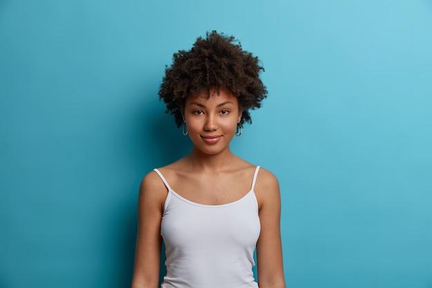 幸せな穏やかな暗い肌のミレニアル世代の女の子は、カジュアルなベストを着て、家で怠惰な週末を過ごし、自信を持って健康に感じ、青い壁に隔離されています。人、ライフスタイル、感情の概念。