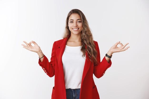 Счастливый спокойный, свободный от стресса современный 25-летний бизнес-леди контролирует чувства руками боком, показывая жест мудра дзен, улыбается мирно с облегчением, медитирует, занимается йогой в офисной красной куртке