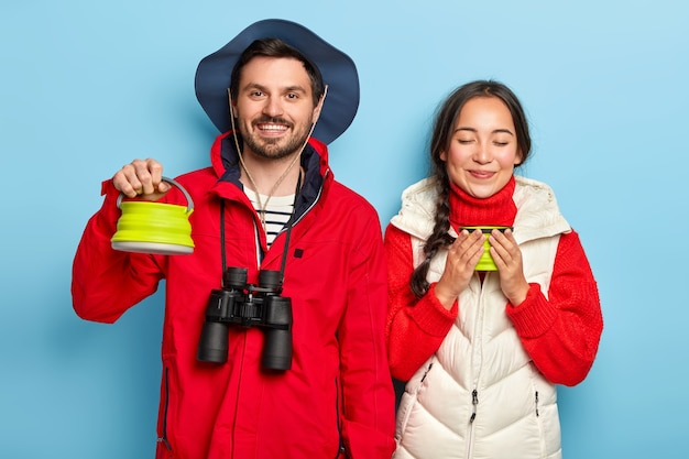 Happy camping couple drink coffee early in morning, spend leisure time in camp site near bonfire, carry binoculars, stop for having break, wear warm outfit, isolated over blue wall
