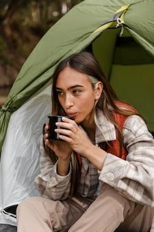 Ragazza di campeggio felice nella foresta che soffia in una tazza