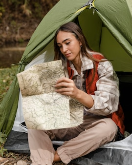 Happy camping girl in the forest checking the map