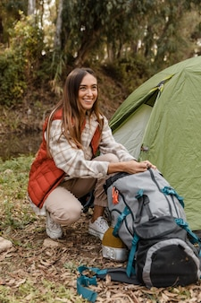 Happy camping girl in the forest searching the backpack