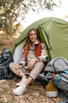 Счастливый кемпинг девушка в лесу, сидя в палатке