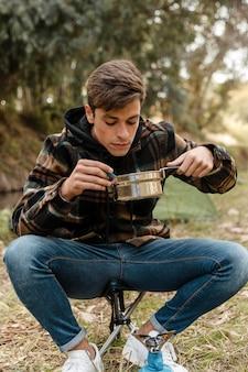 Uomo di campeggio felice nella foresta che mangia