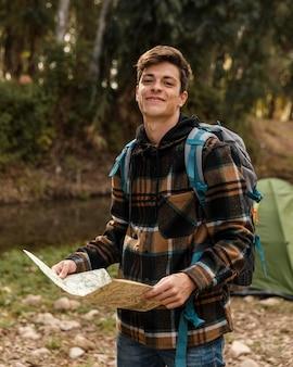 Uomo di campeggio felice nella foresta che tiene la mappa