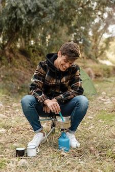 Uomo di campeggio felice nella foresta che produce cibo vista frontale