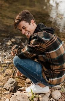 Uomo di campeggio felice nella foresta che si siede sulla riva del fiume