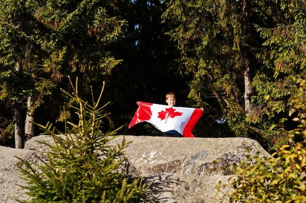 ハッピーカナダデー。山で大きなカナダ国旗のお祝いを持つ少年。