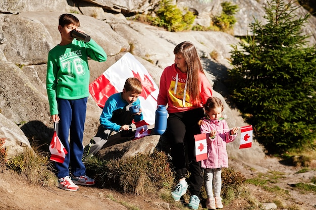 Happy canada day. family of mother with three kids hold large canadian flag celebration in mountains.