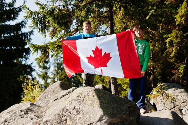 ハッピーカナダデー。山で大規模なカナダ国旗のお祝いを持つ2人の兄弟。