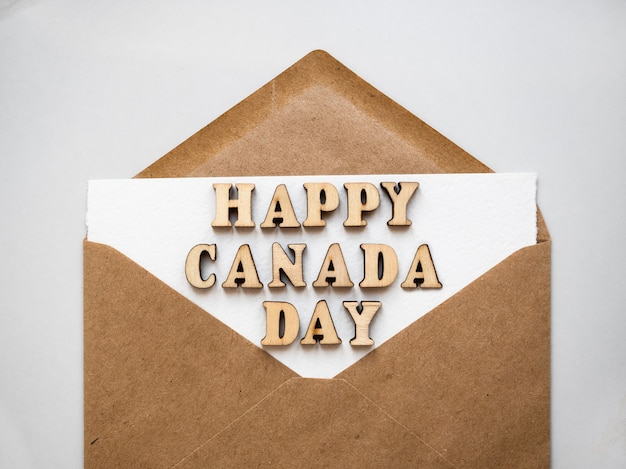 Happy canadian day. postal envelope painted in the national colors of the canadian flag. holiday concept. closeup, top view, texture. congratulations for family, relatives, friends and colleagues