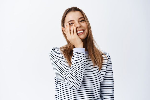 Happy candid girl with natural light make up, touching face and smiling with white healthy teeth, standing carefree against white wall