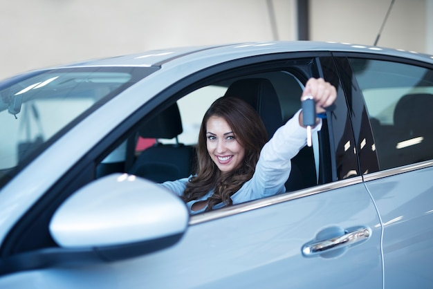 Happy car buyer sitting in new vehicle showing keys in dealership showroom