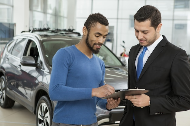 Happy car owner signing papers with professional salesman at the dealership