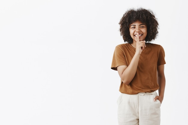 幸せな屈託のないアフリカ系アメリカ人のかわいい10代の少女のスタイリッシュな茶色のtシャツと白いズボンでアフロの髪型でカジュアルに笑みを浮かべて、口の上に人差し指で静かな兆しを見せて