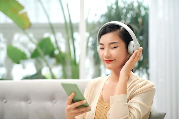 무선 헤드폰을 끼고 눈을 감고 음악을 들으며 소파에 앉아 있는 행복한 평온한 아시아 소녀,
