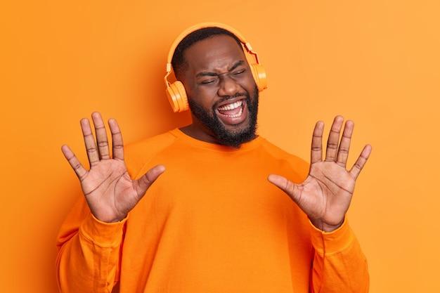 Счастливый беззаботный бородатый мужчина движется в ритме песни, держит ладони поднятыми, носит стереонаушники, ярко-оранжевый джемпер, наслаждается отличным плейлистом.
