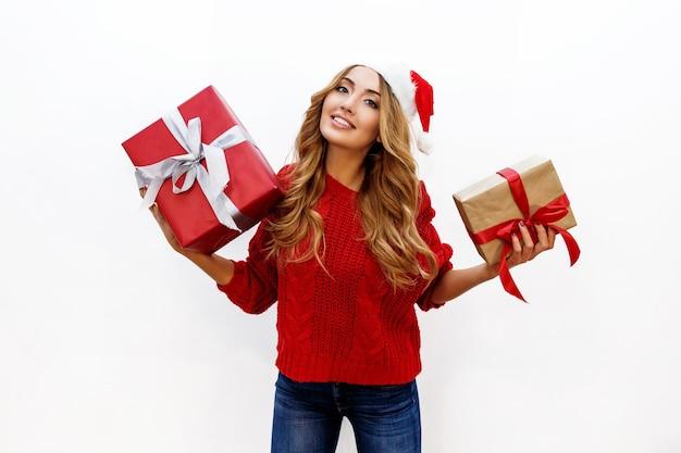 Счастливая беззаботная белокурая женщина празднует новогоднюю вечеринку с подарками. в красной шапке санты и вязаном свитере. позирует