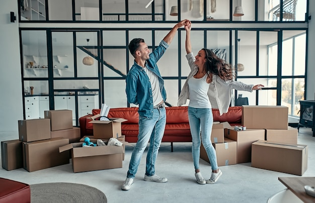 Happy carefree caucasian couple first time home buyers renters owners dancing laughing in living room with boxes together, funny tenants having fun enjoy relocation in new house on moving day.