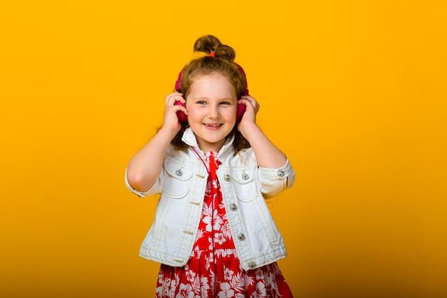 Счастливые беззаботные детские эмоции. энергичная, злая, удивленная радостная очаровательная маленькая девочка на стене.