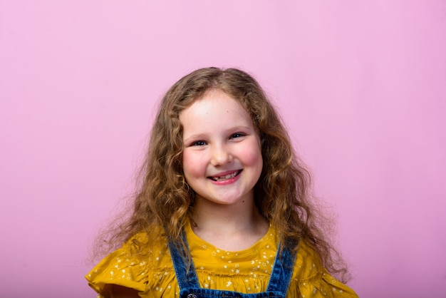 Happy carefree child emotions. energetic joyful adorable little girl laughing at joke on pink background.