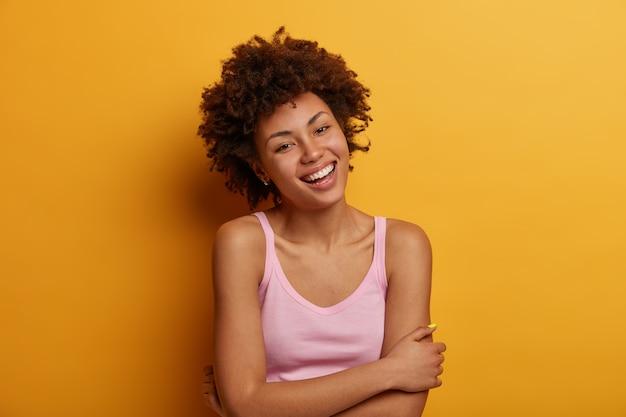 행복하고 평온한 어두운 피부의 사랑스러운 여자는 손을 몸 위로 교차시키고 부드럽게 미소 짓고 낙천적 인 분위기를 가지고 있으며 자연스러운 곱슬 머리를 가지고 있으며 인생에서 즐거운 순간을 즐깁니다.