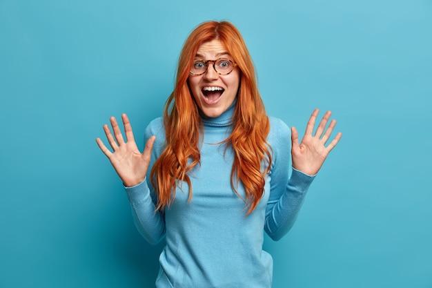 행복한 평온한 감정. 흥분된 빨간 머리 여자는 손바닥을 들고 캐주얼 옷을 입은 행복으로 기꺼이 비명을 지른다.