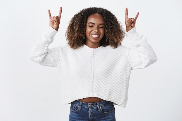 幸せな屈託のない興奮したアフリカ系アメリカ人の縮れ毛の女性目を閉じるスリル満点のショーヘビーメタルジェスチャー手を上げて楽しい笑顔を楽しんで冷やして楽しませてください、白い壁
