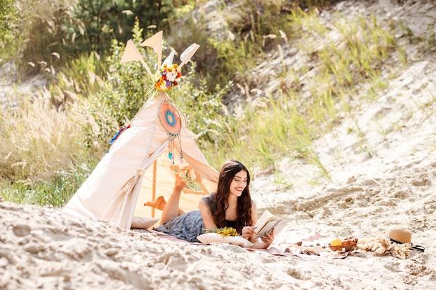 幸せなのんきな女の子は、ウィグワムの装飾の横にある夏の屋外のビーチで時間を過ごしながら本を読んでいます。