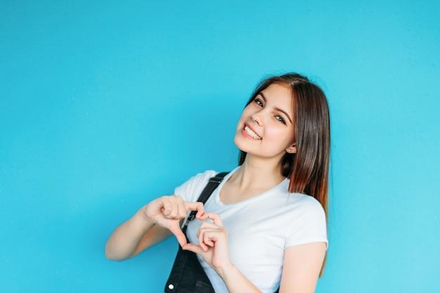 Счастливая беззаботная девушка с темными длинными волосами, одетая в белую футболку, делает сердце изолированным на синем