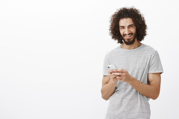 Happy carefree good-looking guy with beard and afro haircut, holding smartphone and laughing