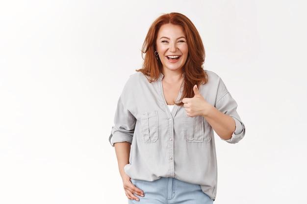 행복한 근심 없는 잘 생긴 빨간 머리 50대 중년 여성이 즐겁게 웃고 즐겁게 지내다 승인 엄지손가락을 치켜세워 만족 좋은 농담 서 있는 흰 벽 환호