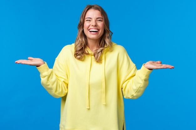 Счастливая беззаботная красивая женщина, короткая стрижка блондинки, держащая обе руки поднятыми в стороны, как будто держит два продукта, дает вам выбор и смех, заискивает два продукта,