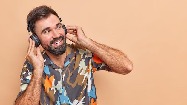 수염이 두꺼운 행복한 평온한 남자는 무선 헤드폰을 통해 음악을 듣습니다.