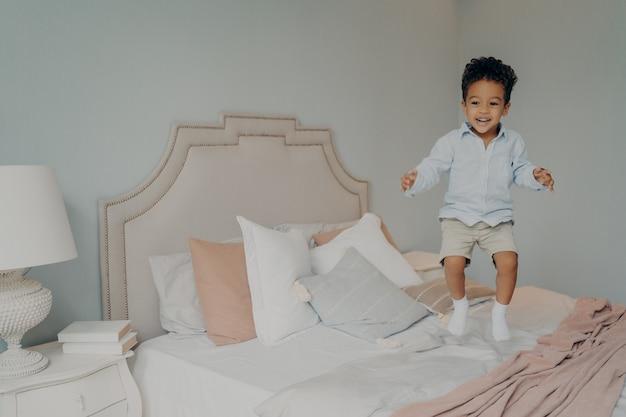 재미 있고 침대에서 점프 캐주얼 옷에 행복 평온한 혼혈 민족 아이 소년