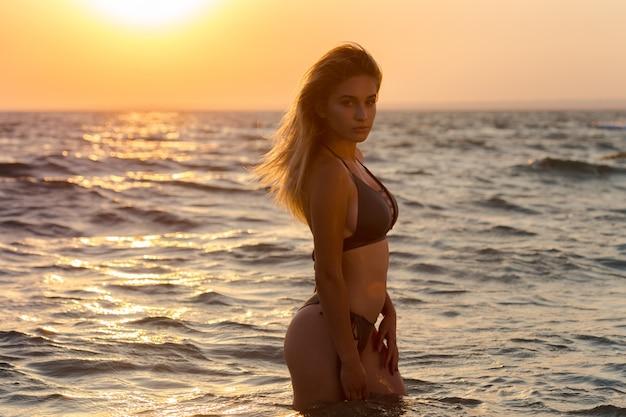 Happy carefree woman on the beach enjoying summer