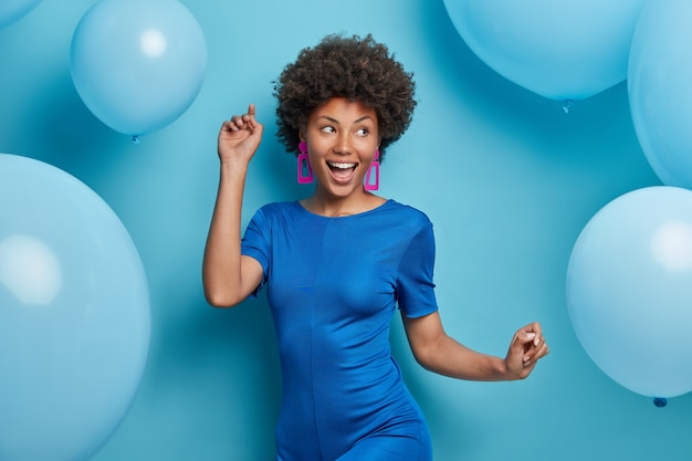 Happy carefree woman dances and has fun dressed in fashionable clothes has festive mood poses against blue balloons
