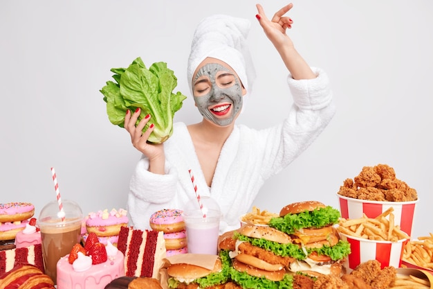 Happy carefree woman dances keeps arm raised and holds green lettuce