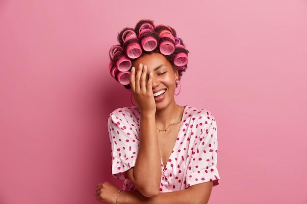 Felice donna spensierata fa il palmo della mano e ridacchia positivamente, essendo di buon umore, vestita casualmente, si prende cura dell'aspetto e dei capelli, indossa bigodini isolati sul muro rosa. la casalinga si prepara per l'appuntamento