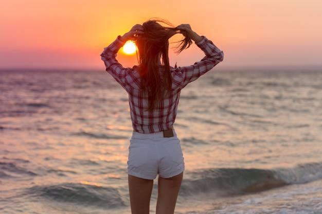 Счастливая беззаботная женщина на пляже, наслаждаясь летом