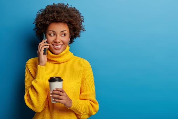 Happy carefree woman talks via mobile phone while drinks coffee, wears yellow sweater