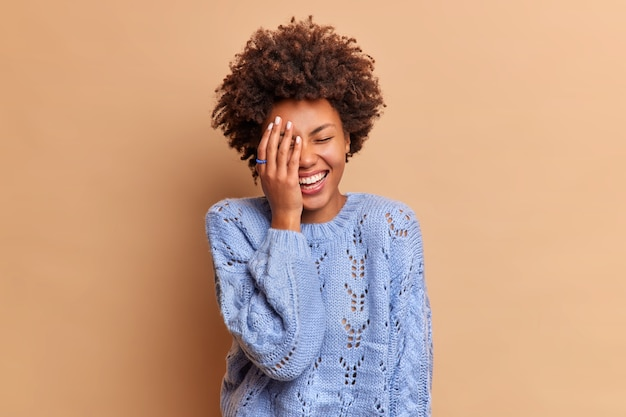 La donna spensierata felice con i capelli ricci ride ad alta voce da una battuta divertente che fa la faccia con la palma guarda qualcosa di esilarante indossa un maglione casual isolato sul muro beige
